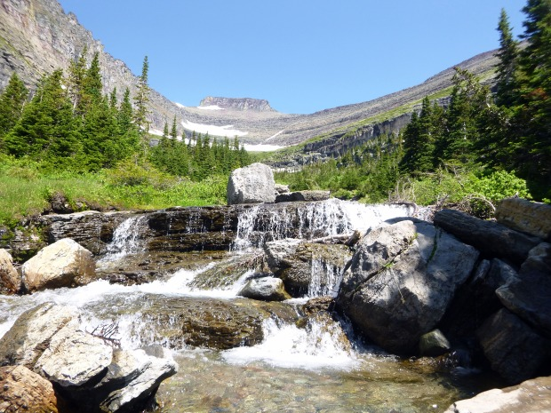 Waterfall with cirque - or carved out mountain - in background, Glacier National Park, MT