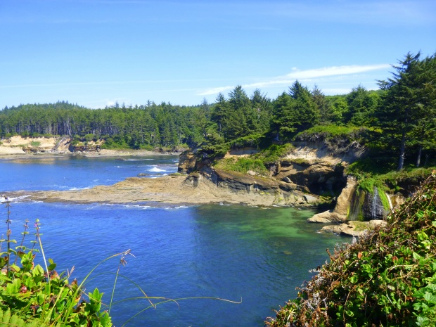 Blue green waters of the Pacific meet eroded sandstone and lush forest, Oregon