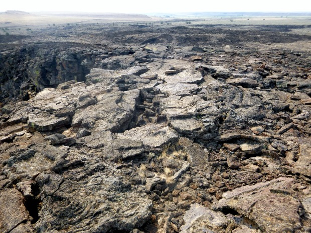 Sides of Lava Pit Crater showing cracked basalt that once welled from the volcanic crater, Diamond Craters, Oregon