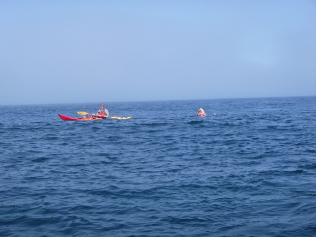 Andrew swimming in the Strait of Juan de Fuca with kayaker Steve Goodsen nearby