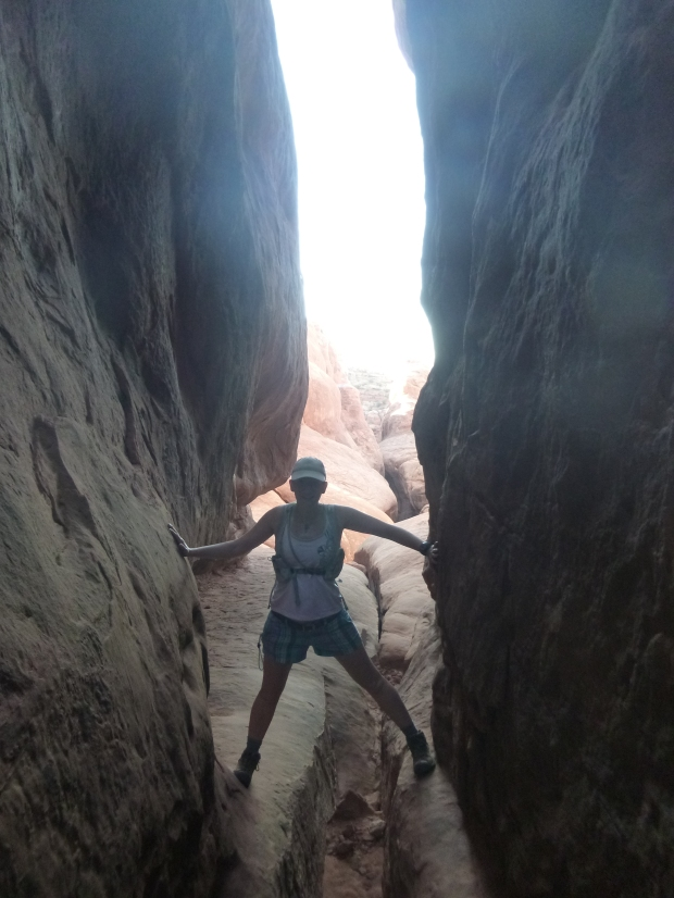 Rachel posing while climbing between fins, Fiery Furnace, Arches National Park, Utah