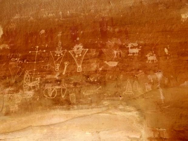 Fremont trapezoidal anthropomorphs (humanoid figures) and animal petroglyphs below older Barrier Canyon red anthropomorphic pictographs, Sego Canyon, Utah