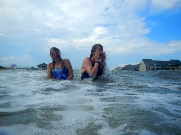 Carrie and Rachel tossed around by waves, Oak Island, North Carolina