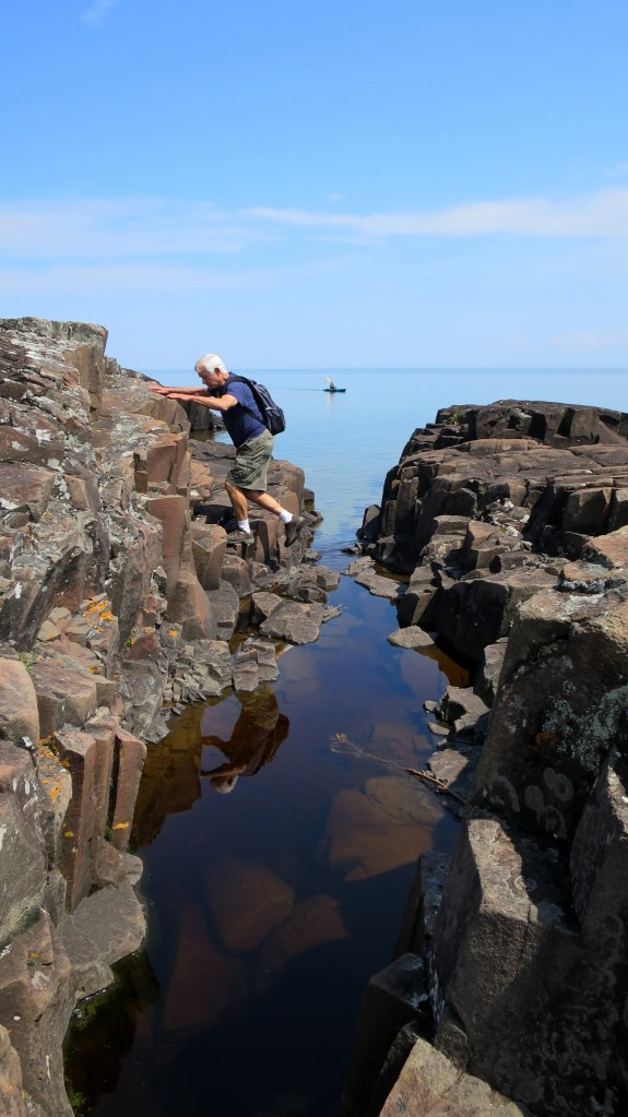 Tom crossing over fissures in the rock, Artists' Point, Grand Marais, Minnesota