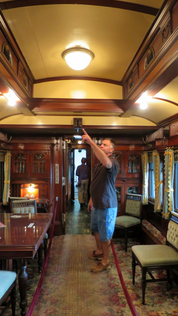 Robert gesturing to fine mahogany woodwork in the interior of the rail car, Adirondack Museum, Blue Mountain Lake, New York