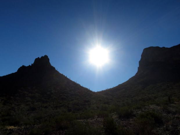 Sun over the middle of the saddle; Picacho Peak on left. Near trailhead of Hunter Trail, Picacho Peak State Park, Arizona