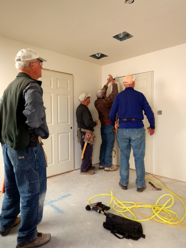Lowell, Hans, Tony, and I watching construction supervisor Pete adjust a persnickety door, Mesilla Valley Habitat for Humanity, Las Cruces, New Mexico