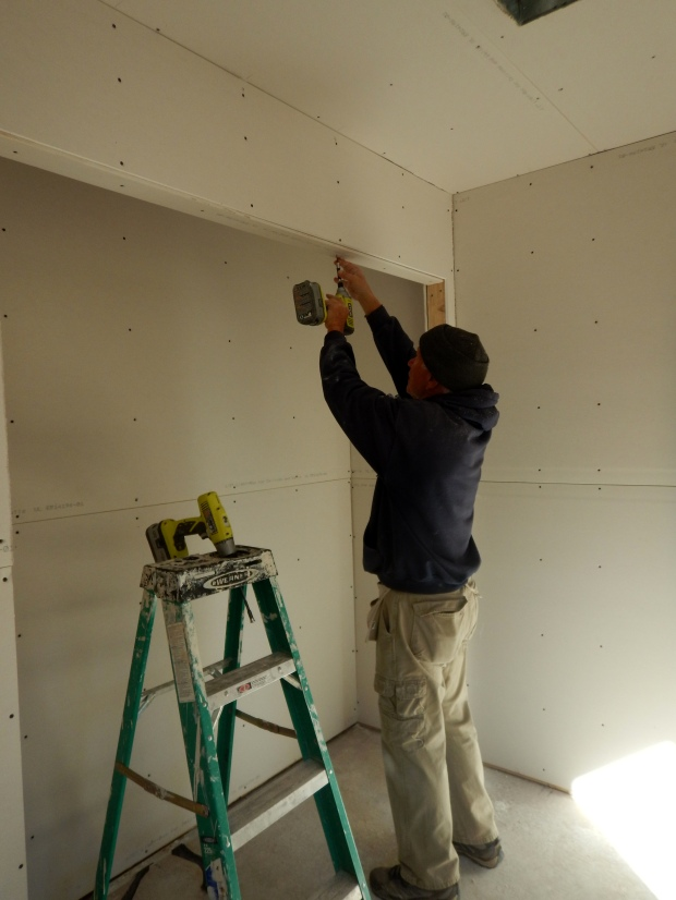 Tom screwing in strips of sheetrock around bedroom closet, Mesilla Valley Habitat for Humanity, Las Cruces, New Mexico