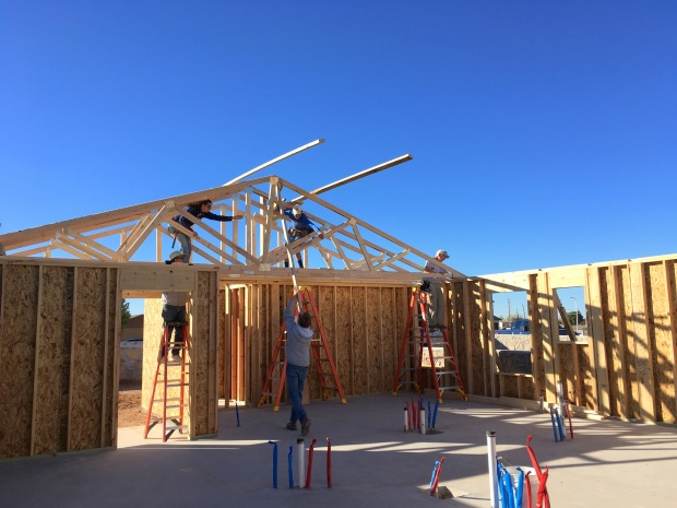 Some of the first trusses going up: Jake and Angela secure them from the middle after Pete swings them up and Tom sets them on the right