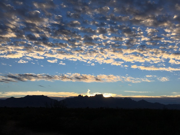 Sun illuminating the clouds over the Organ Mountains