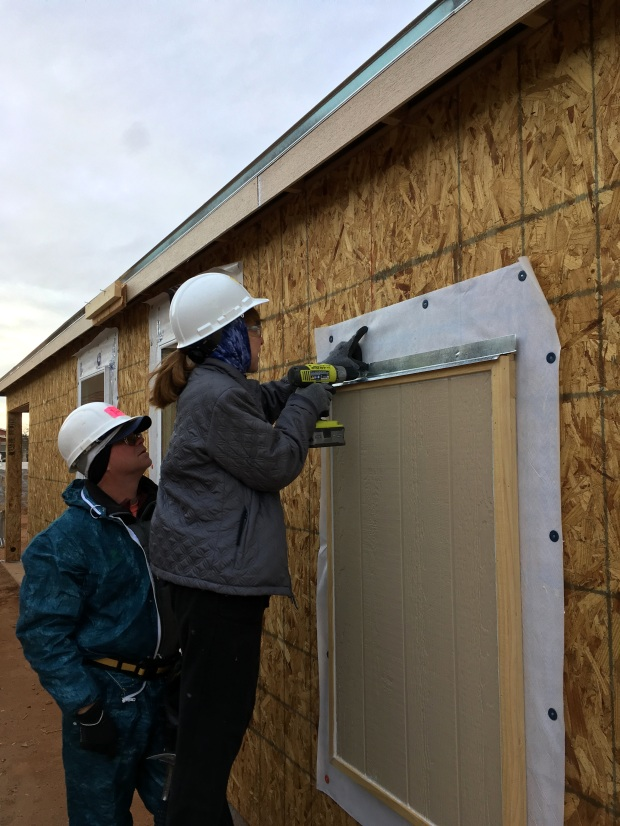 Chris and Doug screwing in drip edge over where the electrical box will be mounted