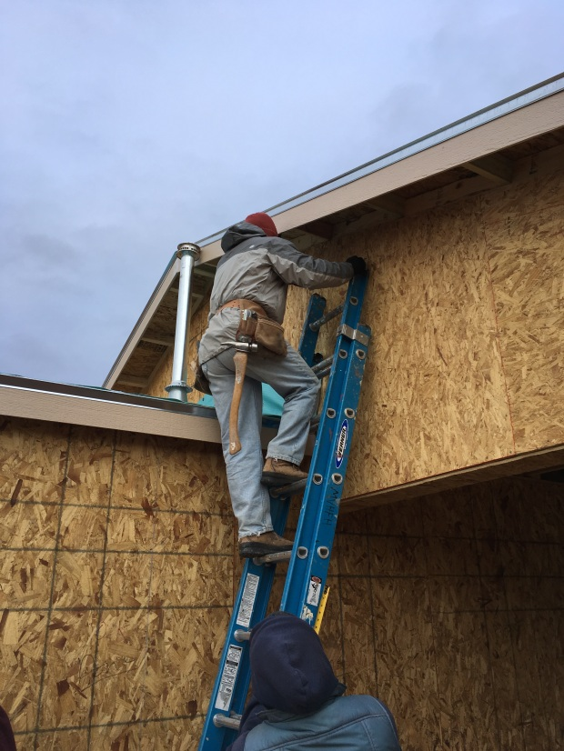 William heading up to the roof so Kit, Tom, and I can hand up the end of the soffit