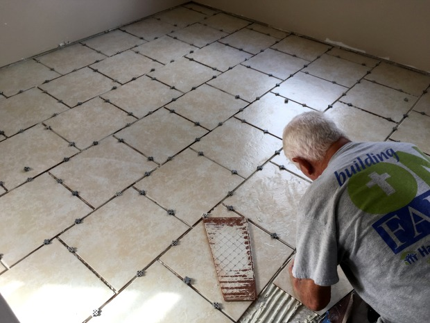 Tom placing the last tiles in the kitchen/dinette