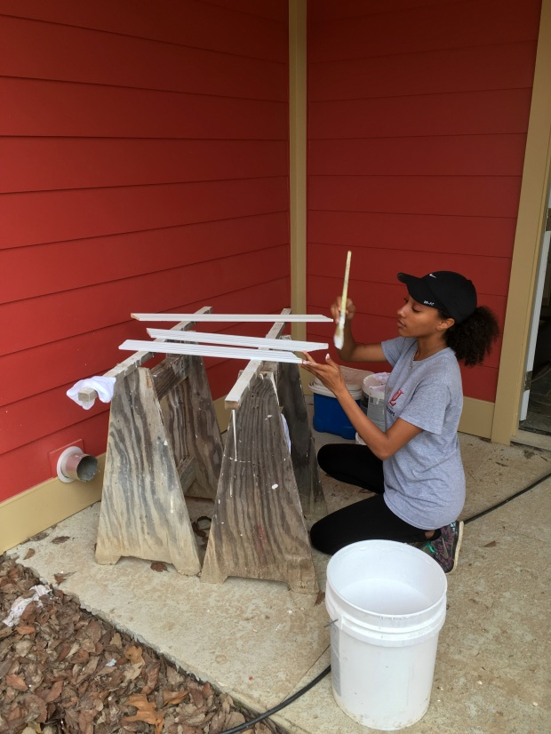 Americorps volunteer Rain painting trim